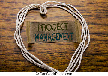 Conceptual hand writing text caption Project Management. Business concept for Strategy Plan Goals written on sticky note paper on the dark wooden background. With heart meaning love or adoration.