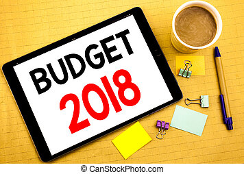 Conceptual hand writing text caption showing Budget 2018. Business concept for Household budgeting accounting planning Written on tablet laptop, wooden background with sticky note, coffee and pen
