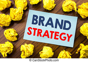 Conceptual hand writing text inspiration showing Brand Strategy. Business concept for Marketing Idea Plan written on sticky note paper on the wooden background with folded yellow paper