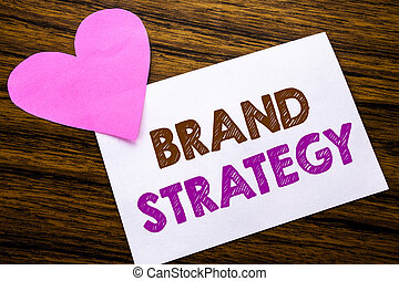 Conceptual hand writing text showing Brand Strategy. Concept for Marketing Idea Plan written on sticky note paper, wooden wood background. With pink heart meaning love adoration.