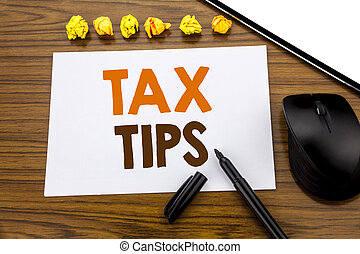 Conceptual hand writing text showing Tax Tips. Business concept for Tip Forn Taxes written on sticky note paper on the wooden background with marker mouse and tablet office view.