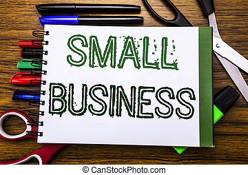 Conceptual hand writing textSmall Business.  Concept for Family Owned Company Written on notebook, wooden background with office equipment like pens scissors colourful marker