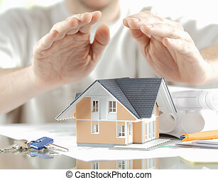 Conceptual Hands Covering Miniature Model Home