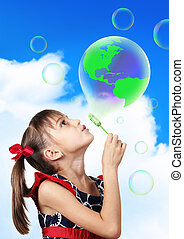 conceptual image, Child girl blowing soap bubble forming green globe earth