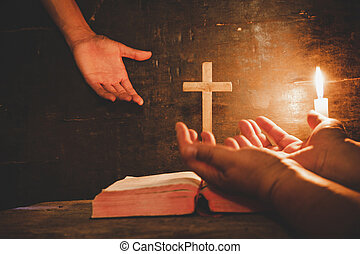 conceptual image focus on candle light with man hand holding wooden cross on stack of bible and blurred world globe in the dark room, christian symbol show Jesus is the light of the world