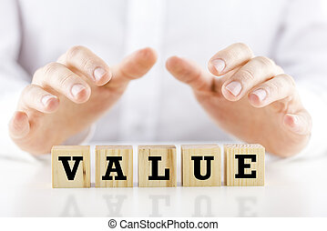 Conceptual image of a businessman in shirtsleeves holding his hands protectively above a line of wooden cubes with the word - Value.
