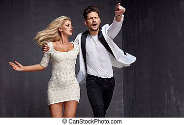 Conceptual image of an attractive couple chasing somebody