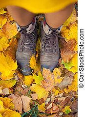 legs in boots on the autumn leaves