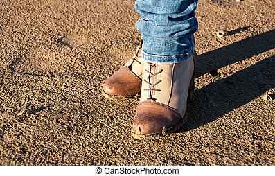 Conceptual image of legs in boots on the autumn