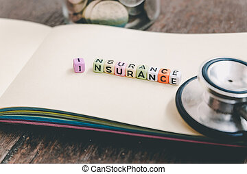 conceptual image with INSURANCE word block on note pad. coin in glass jar and used stethoscope. soft focus background