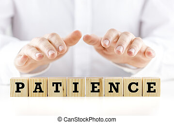 Conceptual image with the word Patience on wooden blocks or cubes protected by the hands of a man sheltering them from above