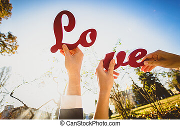 """Conceptual photo of man and woman holding halves of """"Love""""..."""