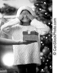 conceptual photo of mother making daughter a surprise on Christmas