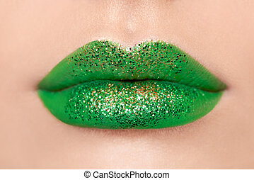 Conceptual photo of St. Patrick's Day. Close up view of woman lips with green lipstick. Holiday makeup