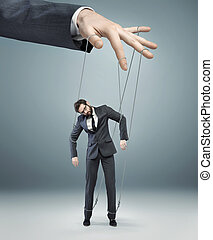 conceptual picture of a boss pulling the strings -...