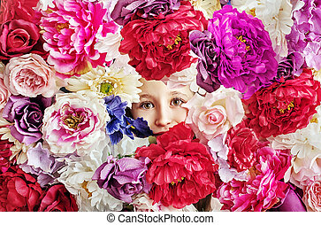Conceptual picture of girl behind a flower wall