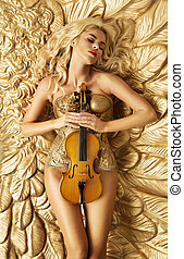 Conceptual picture of golden woman holding a violin