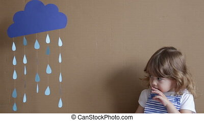 Little girl on gray background play with drop shapes and cloud