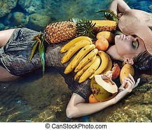 Conceptual portrait of a lady with tropical fruit