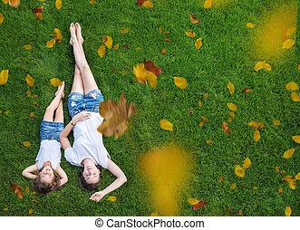 Conceptual portrait of a mother relaxing with daughter on a fresh, green lawn