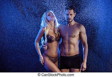 conceptual portrait of a sensual couple posing in the rain