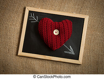 knitted heart lying on arrow drawn by chalk