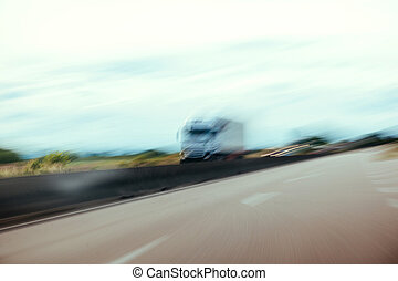 Conceptual silhouette of a defocused truck in motion on highway