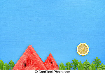 Conceptual summer landscape with watermelon, lemon and green leaves on blue table