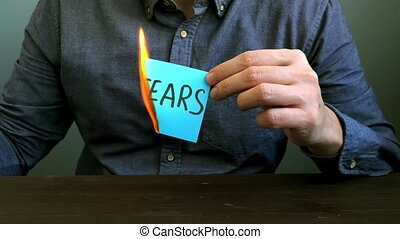 Conceptual video of the fight against fear. A man burns a sheet with the inscription.