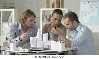 Conceptuality - Three architects dealing with paper models,...
