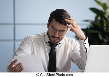 Concerned business owner reading letter from bank about financial problems