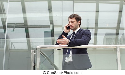Concerned Businessman Talking on a Mobile Phone in Modern...