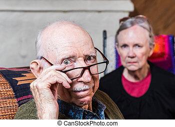 Concerned Elderly Couple - Concerned elderly couple sitting...