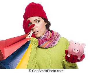 Concerned Expressive Mixed Race Woman Wearing Winter Clothing Holding Shopping Bags and Piggybank Isolated on White Background.