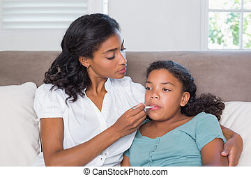 Concerned mother taking her daughters temperature