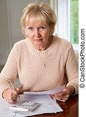 Concerned Senior Woman Reviewing Domestic Finances