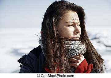 Concerned woman outdoors traveling in winter icy landscape