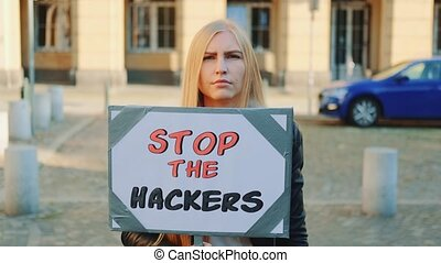 Concerned woman with protest banner calling to stop hackers by walking on the city street