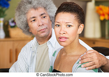Concerned Woman with Spouse - Concerned young woman with...