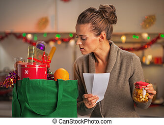 Concerned young housewife with checks exploring christmas...