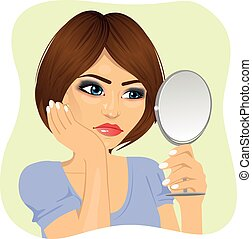 Concerned young woman looking at herself in mirror