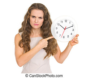 Concerned young woman pointing on clock