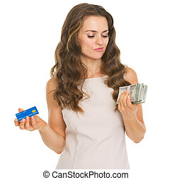 Concerned young woman with credit card and dollars