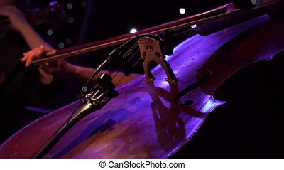 Concert, a woman musician hand playing the cello on stage, hand close up.