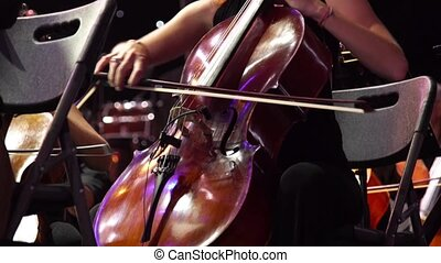 Concert, a woman musician playing the cello on stage with a lot of colleagues.