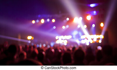 Concert audience, out of focus with stage lights and colors.