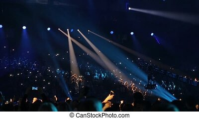 Concert hall with spectators. Professional lighting equipment on stage during a performance of popular artist. Viewers shoot the artist on mobile phones in the concert hall.