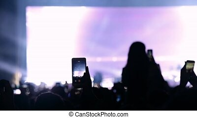 Concert live streaming mobile phone hand.