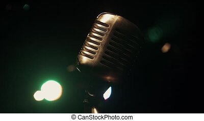 Concert metal gleam microphone stand on stage in retro bar. Green spotlights.