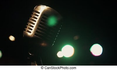 Concert metal gleam microphone stand on stage in retro club. Green spotlights.